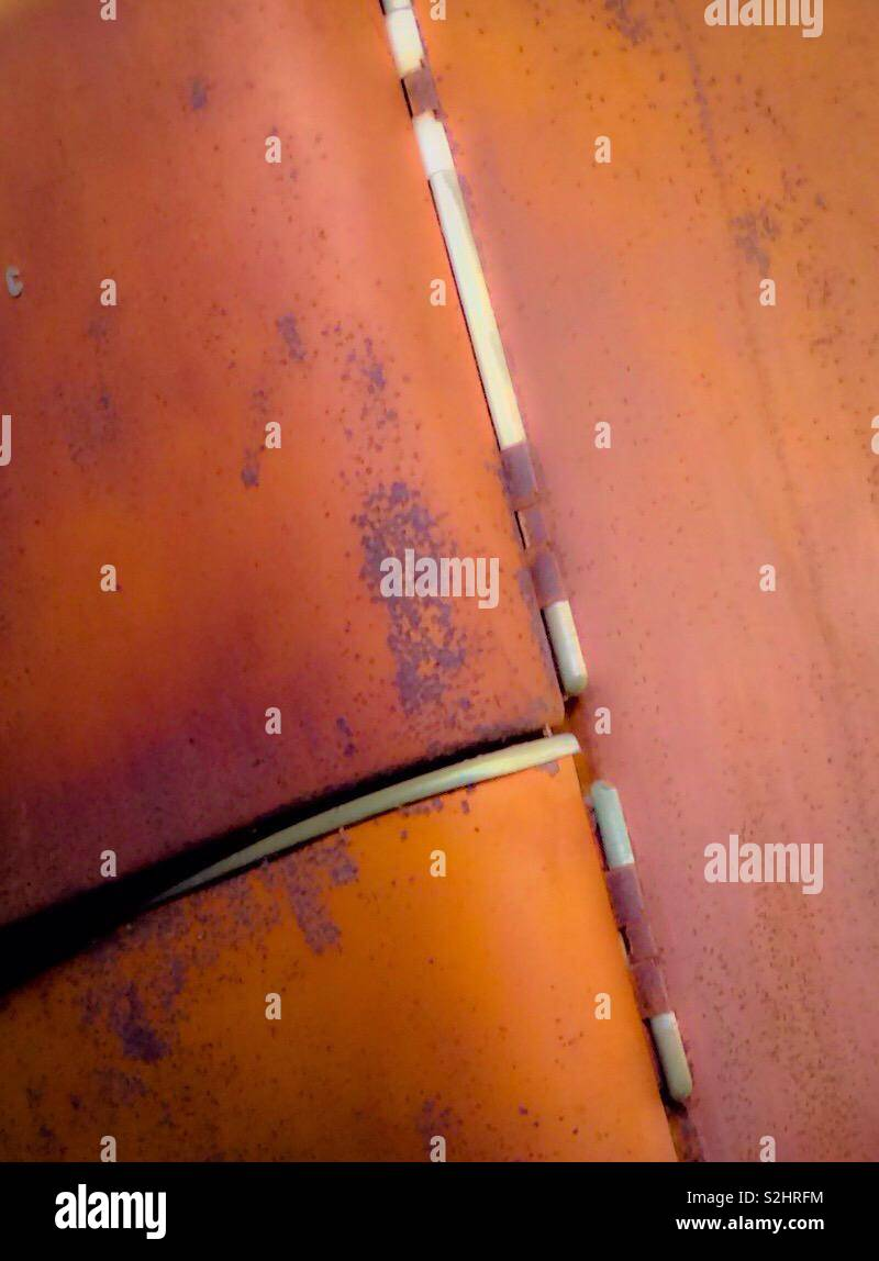 De couleur orange vif sur la rouille vieux réfrigérateur Photo Stock