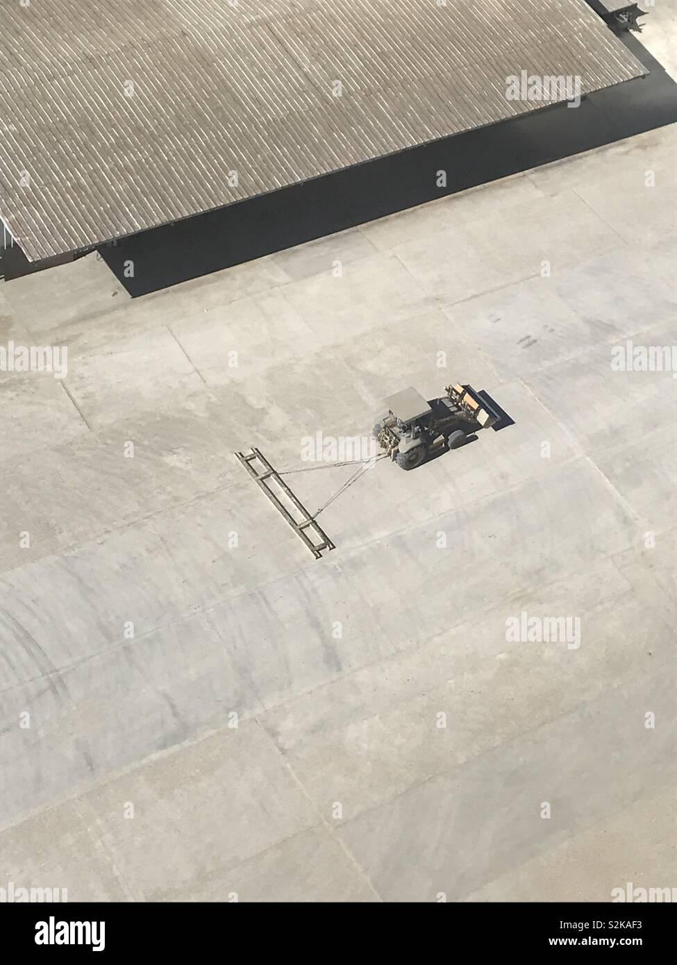 Le tracteur se déplace d'un site à l'autre faisant glisser une barre de lissage du béton. Photo Stock