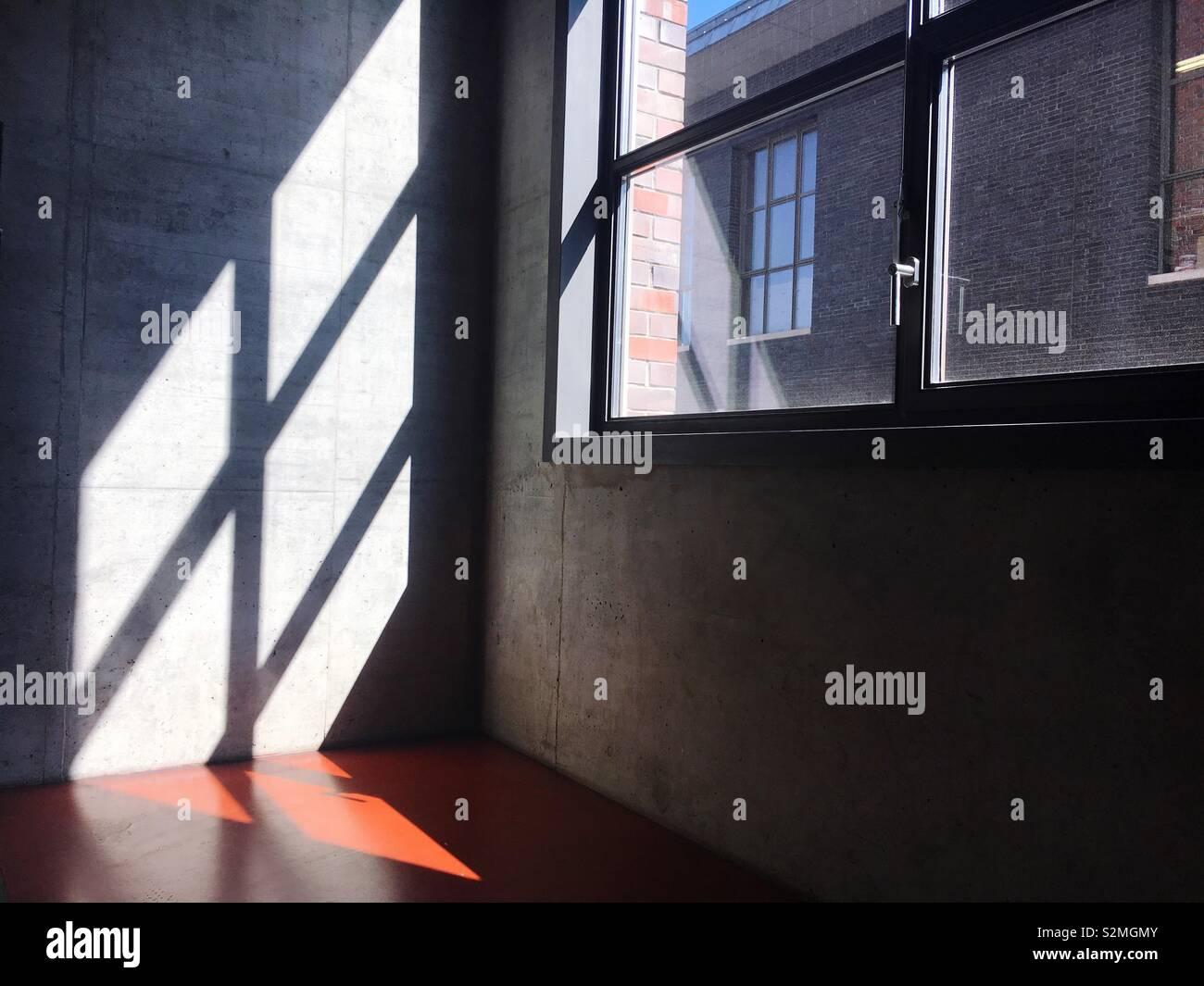 La lumière du soleil brillant à travers une fenêtre sur un mur de béton Photo Stock