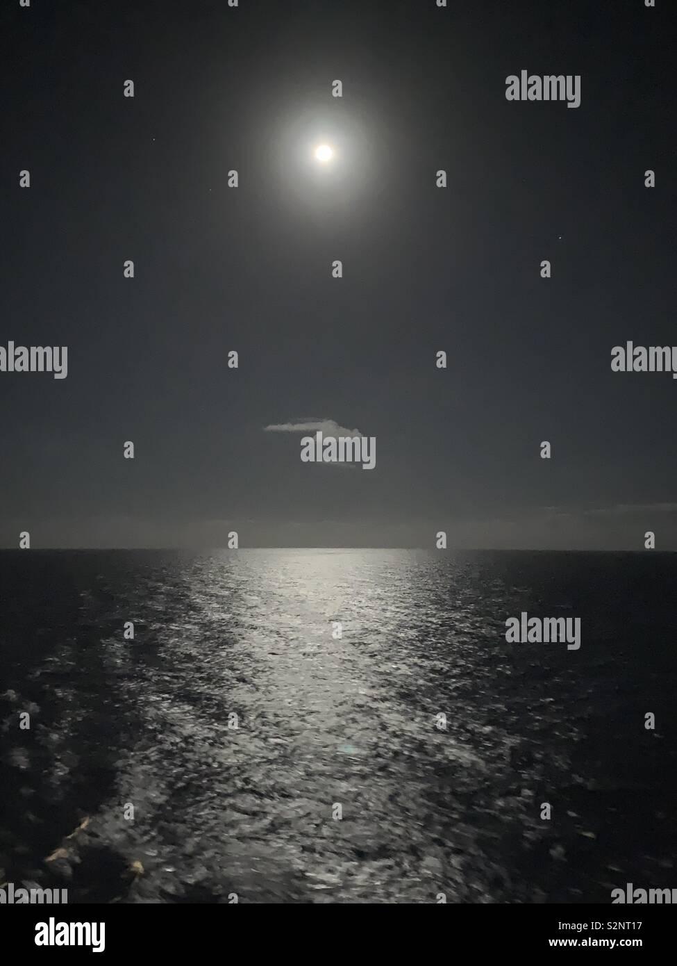 Lune miroitant à la surface de la mer avec un nuage vaporeux prises sur la mer des Caraïbes Banque D'Images