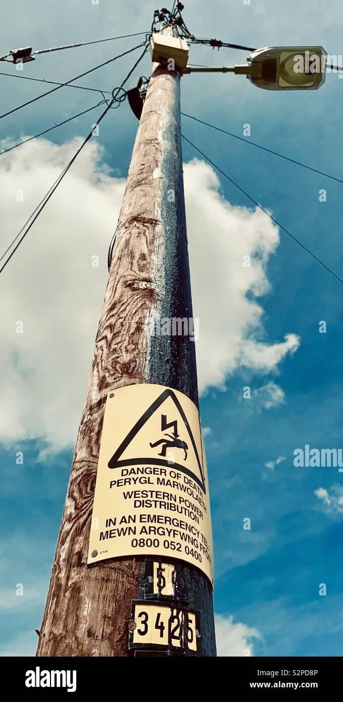 Poteau d' électricité avec bi-lingue Anglais/Gallois panneau d'avertissement de danger de mort Banque D'Images