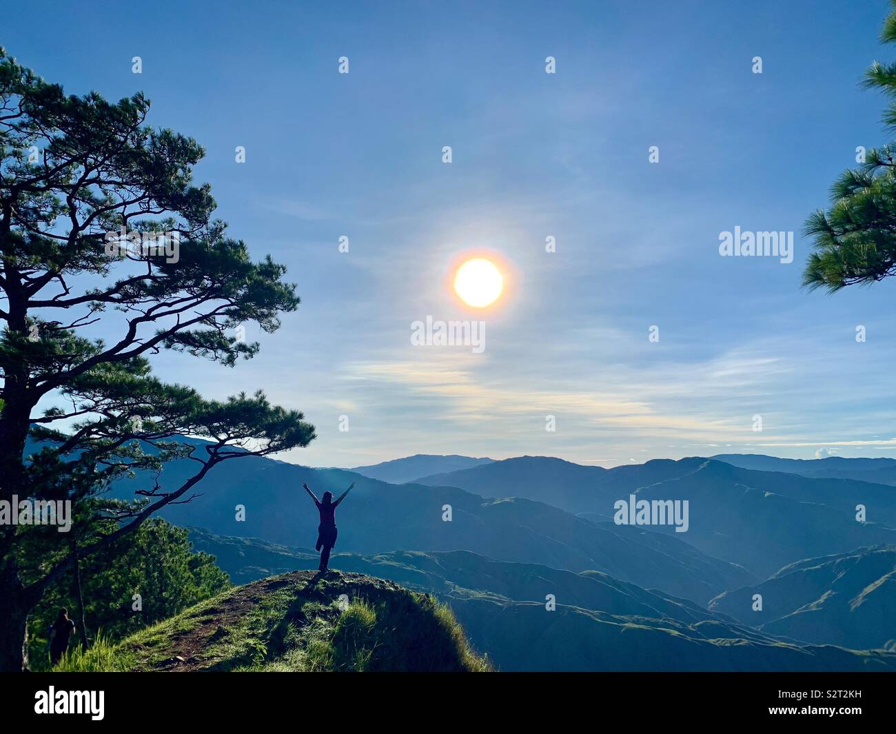Femme jouant au sommet de la montagne au lever du soleil Photo Stock