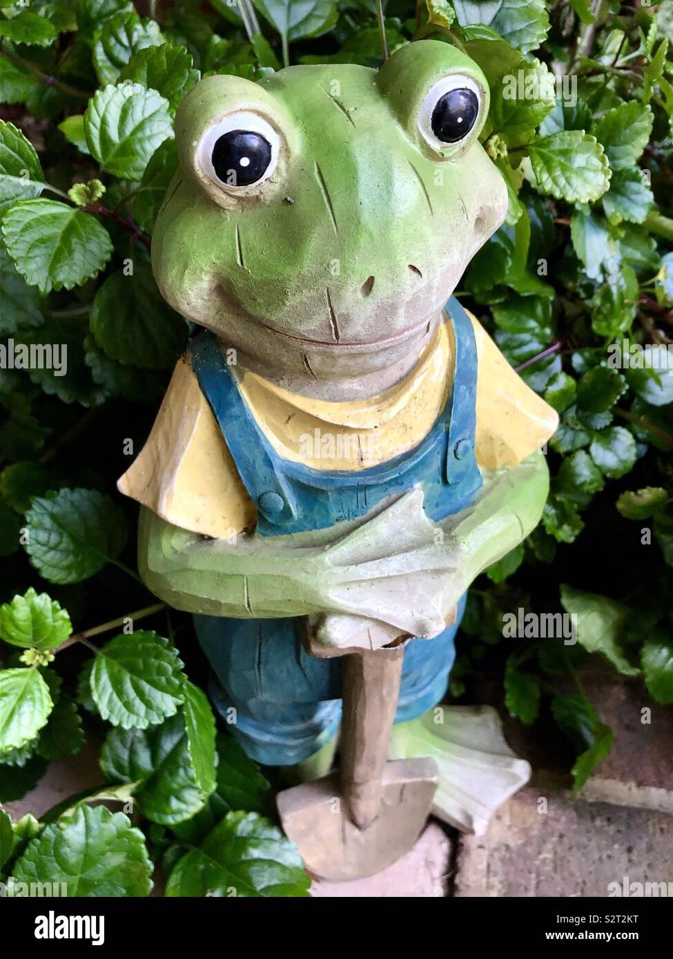 Statue grenouille verte habillé en salopette et chemise jaune avec une pelle dans la main prête pour journées de travail Photo Stock
