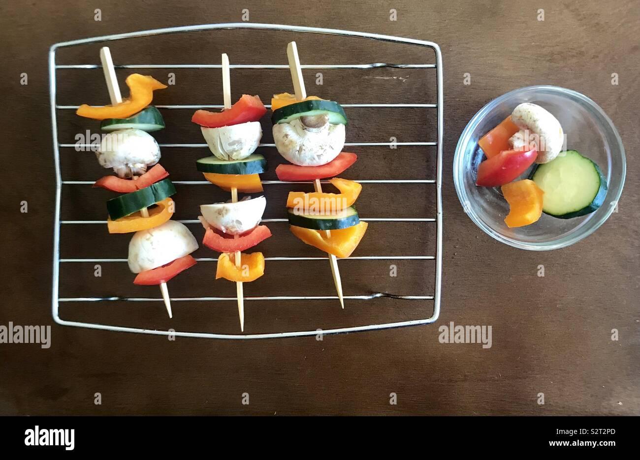 Un rack de métal avec des brochettes de légumes préparés et un bol en verre avec des morceaux de légumes de concombres, champignons, poivrons et Photo Stock