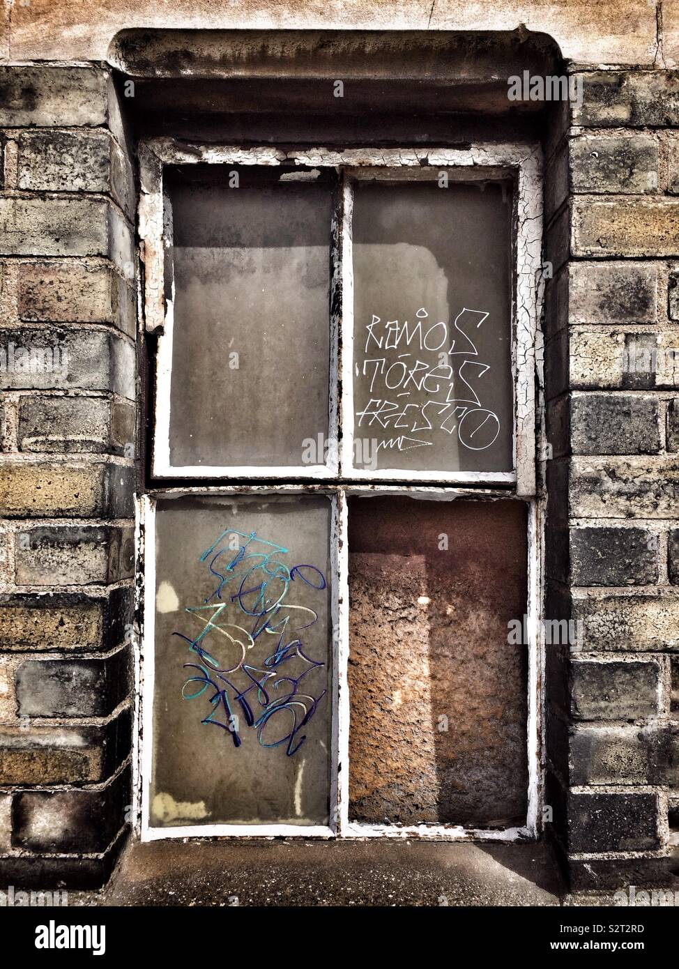 Une vitre cassée couvert de graffitis dans un entrepôt désaffecté à Tottenham, Londres. Photo Stock