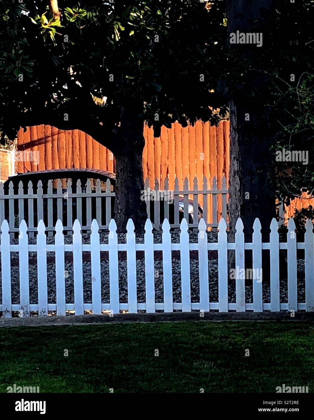 Une soirée tranquille coucher du soleil se reflète sur une clôture derrière une clôture blanche. C'est la vie en banlieue à son meilleur. Photo Stock