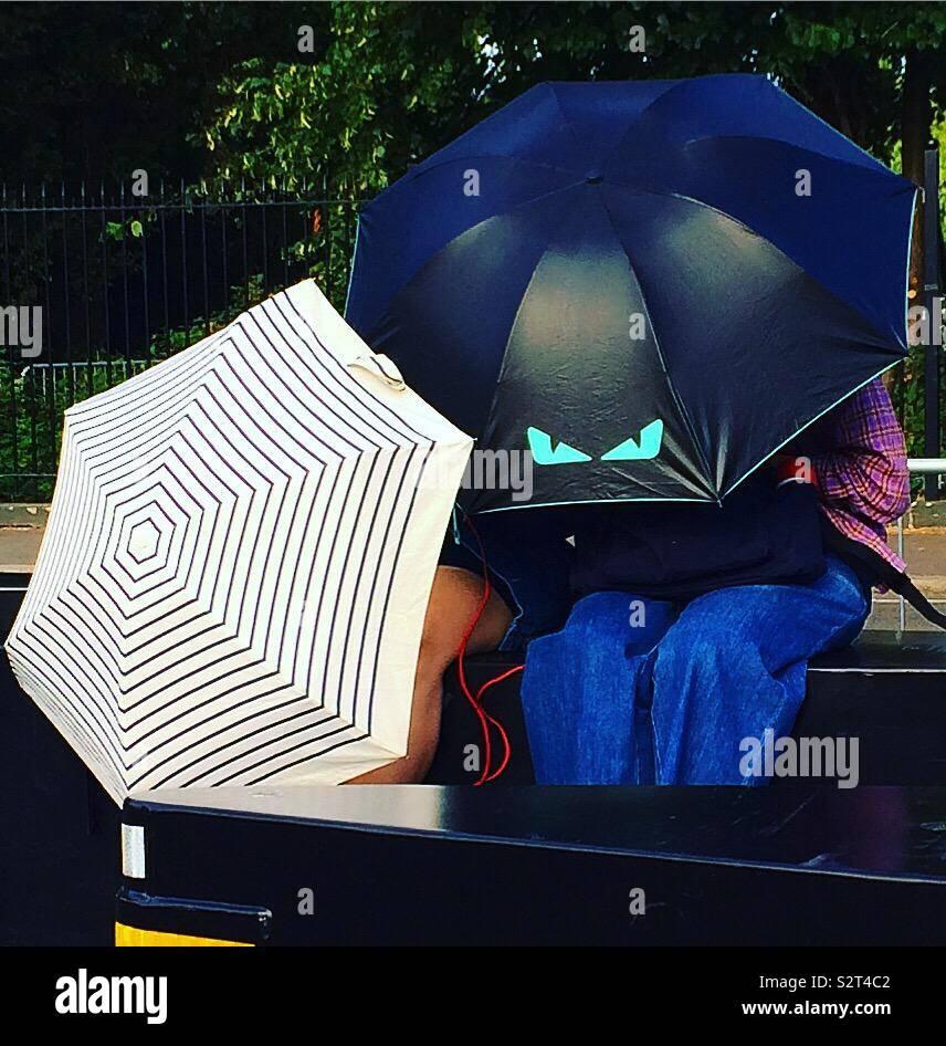S'abritant sous des parapluies Photo Stock