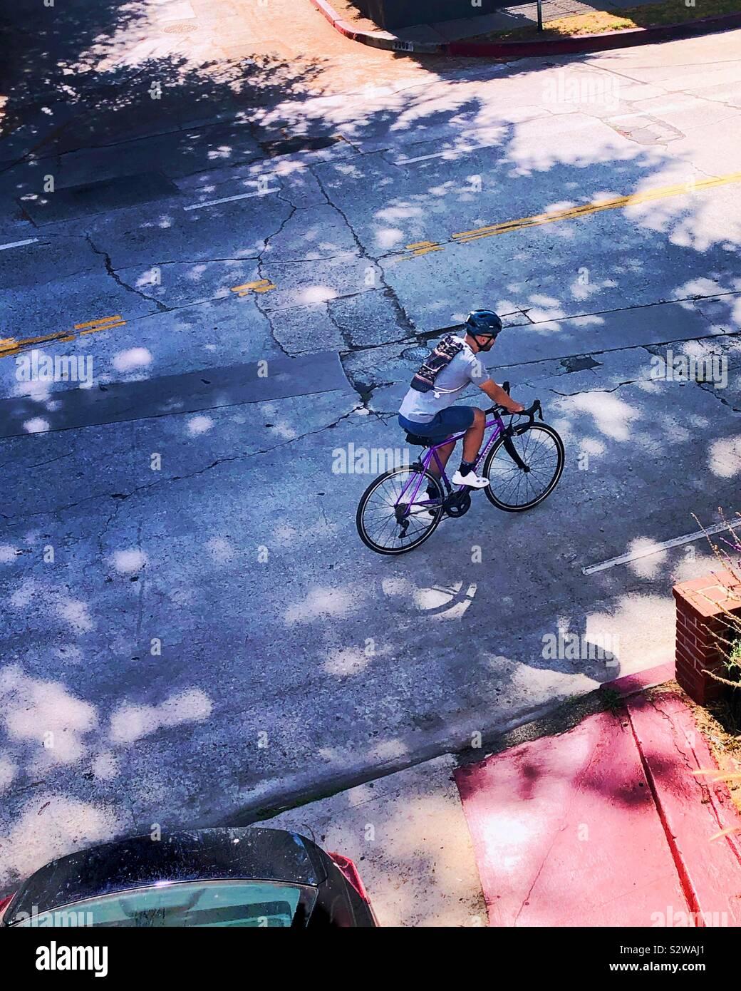 Un cycliste solitaire aspire la forte pente en face de notre terrasse. Banque D'Images
