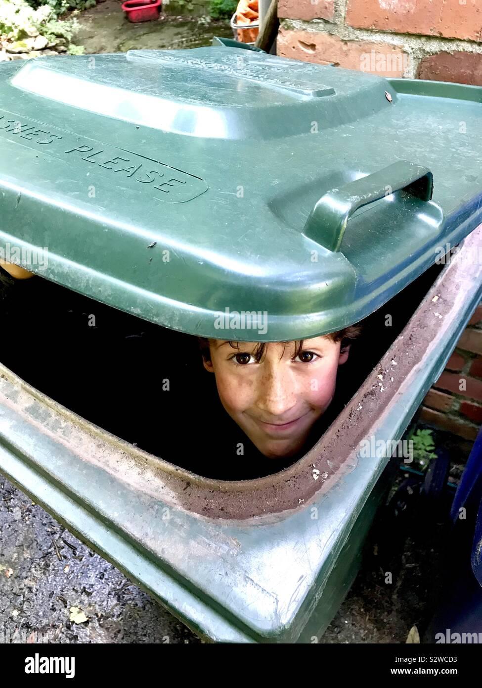 Un garçon se cache dans une poubelle sur roues barrée. Banque D'Images