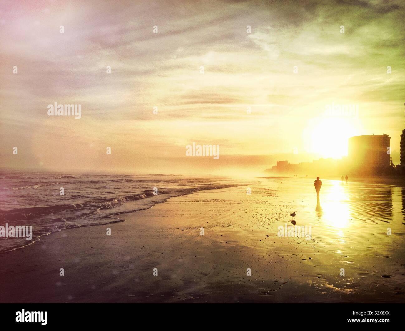 Les gens qui marchent sur la plage pendant le coucher du soleil à Myrtle Beach en Caroline du Sud. Banque D'Images