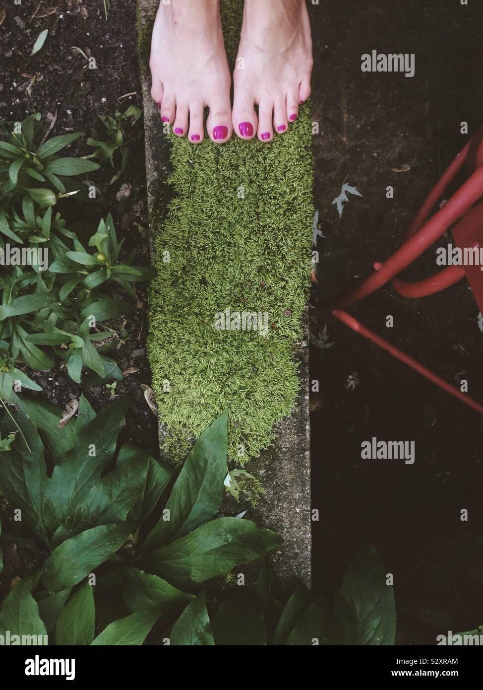 Fille debout sur un diviseur de parpaing moussue dans un jardin. Banque D'Images