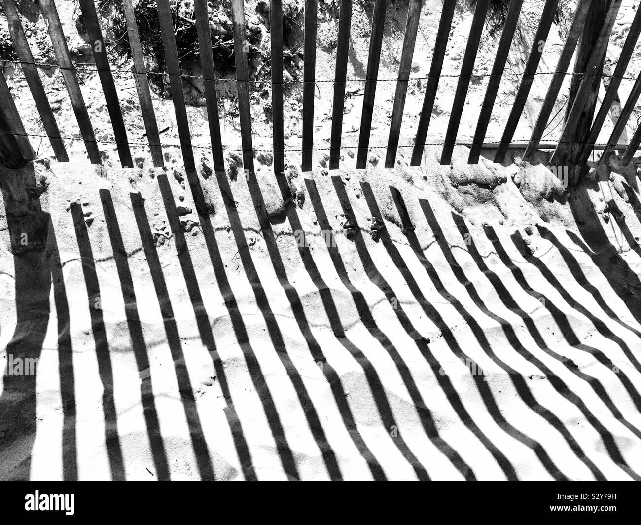 Une clôture en bois le long d'un sentier de sable menant à la plage a son ombre formant un motif abstrait dans le sable. Banque D'Images