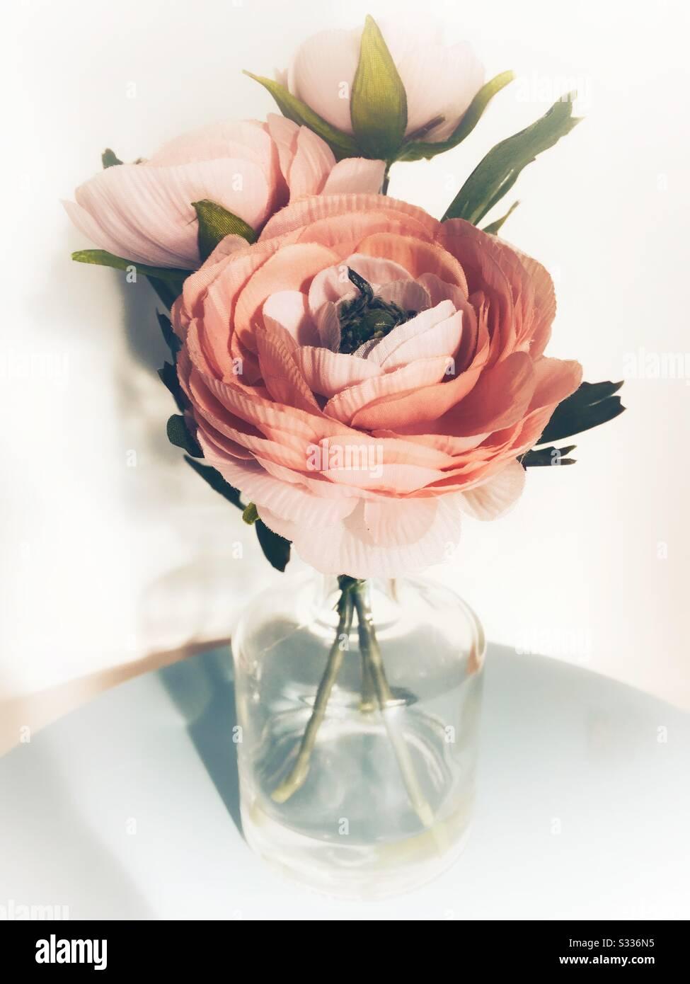 Fleurs artificielles en soie dans vase en verre Banque D'Images