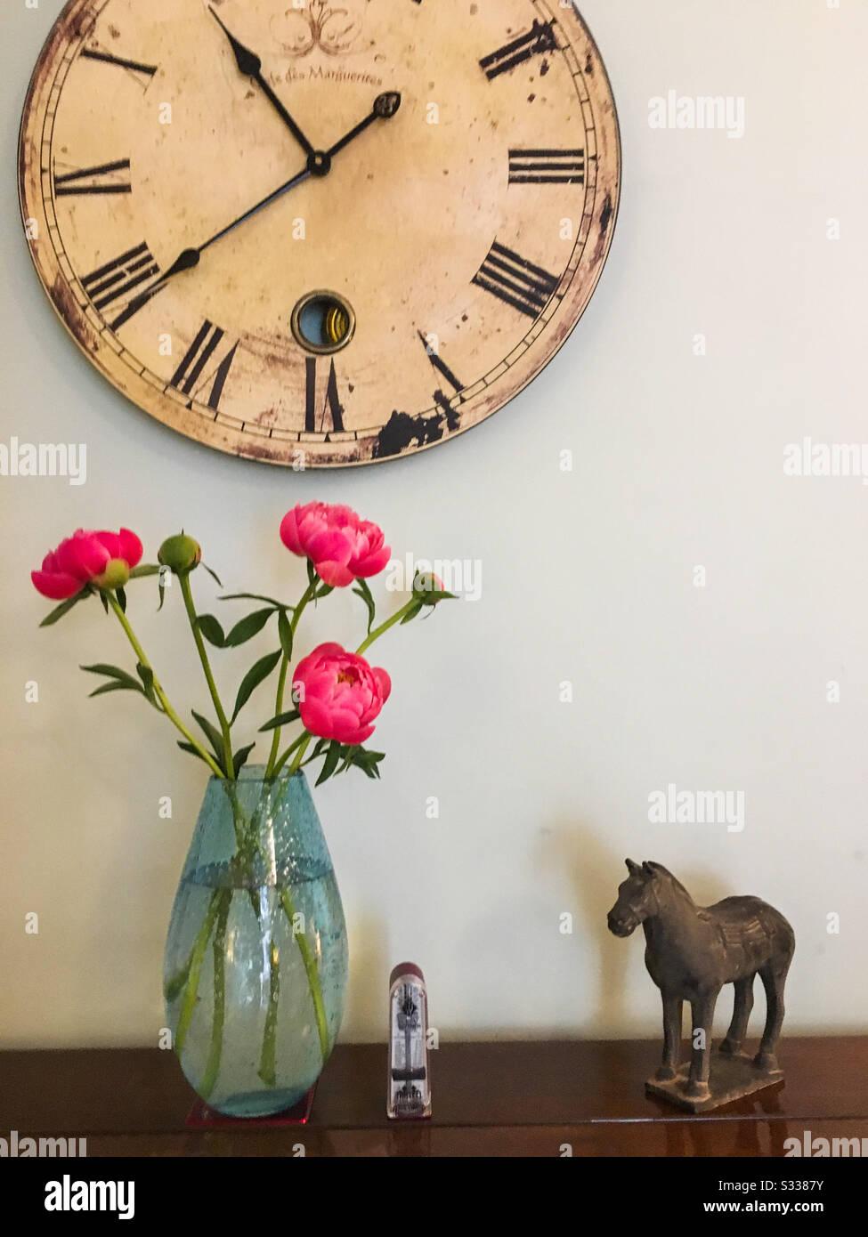 Une photo de vie fixe avec des fleurs pivoines, une horloge, un métronome et un ornement oriental de cheval. Banque D'Images