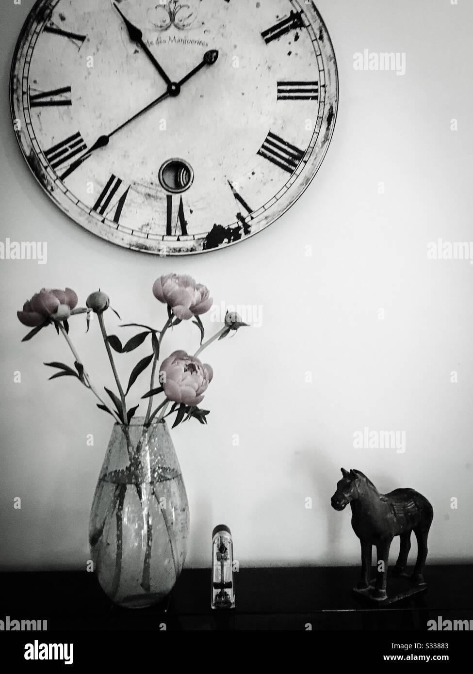 Une photographie de vie noire et blanche d'une horloge, un ornement oriental de cheval, un métronome et un vase de fleurs pivoines, tous placés sur un piano. Banque D'Images