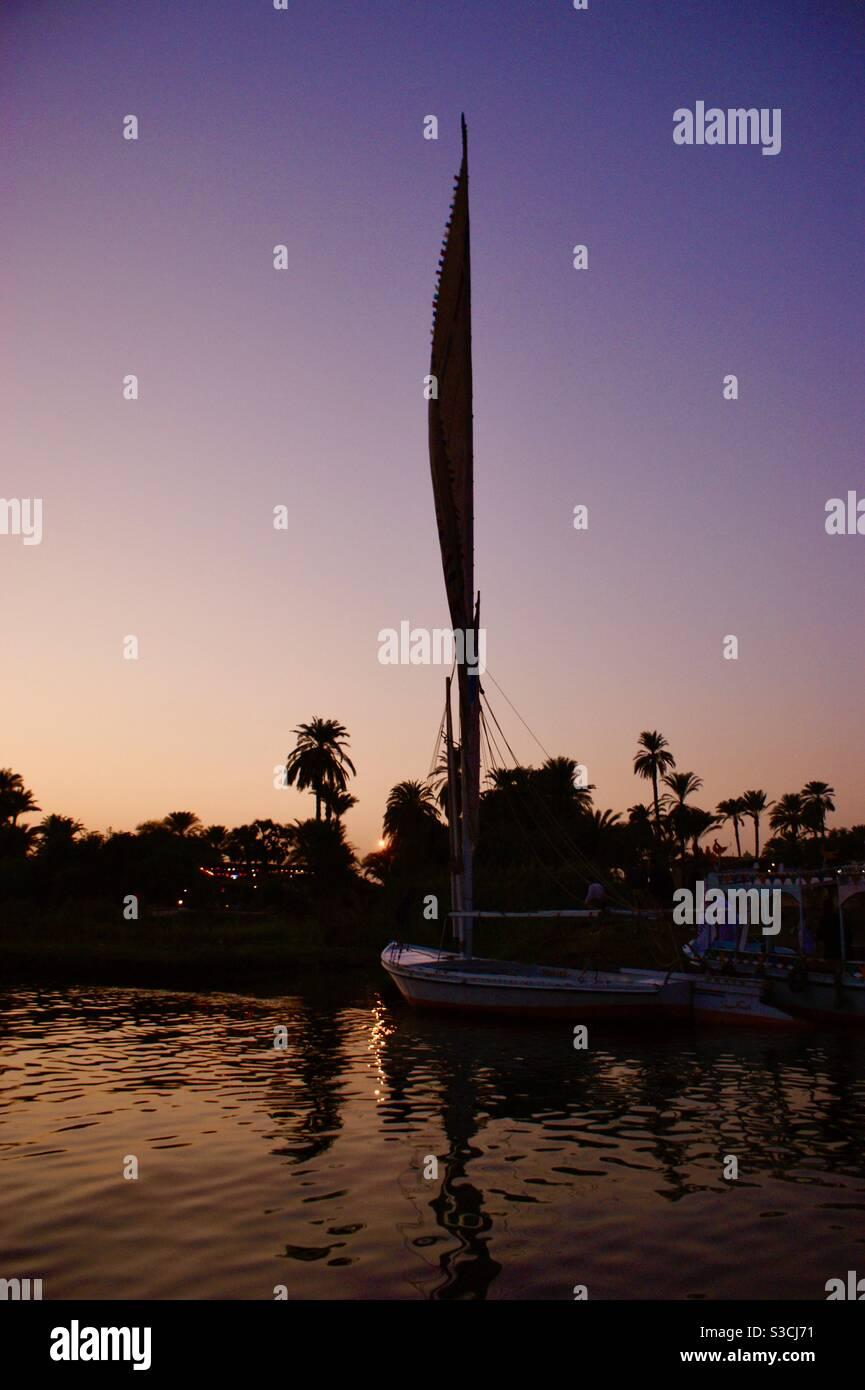 Magnifique et élégant felucca bateau traditionnel naviguant sur le Nil au coucher du soleil près de Louxor, Egypte Banque D'Images