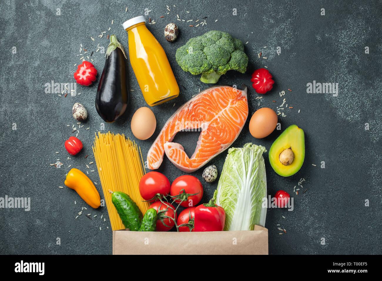 Supermarché. Sac de papier plein d'aliments sains sur une base de béton foncé. Vue d'en haut. Mise à plat. Banque D'Images