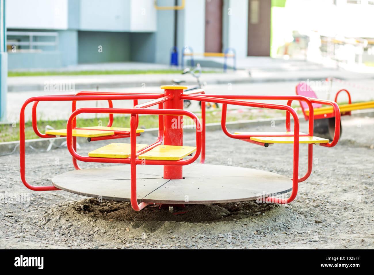 Carrousel rouge sur l'aire de jeux dans la ville. La notion d'enfance, parentalité, jeu Banque D'Images
