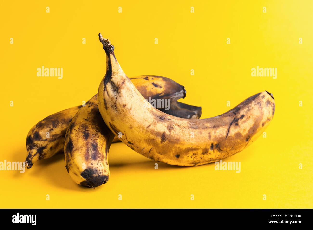 Close-up trois bananes trop mûres laid noircie sur fond jaune. Photo Stock