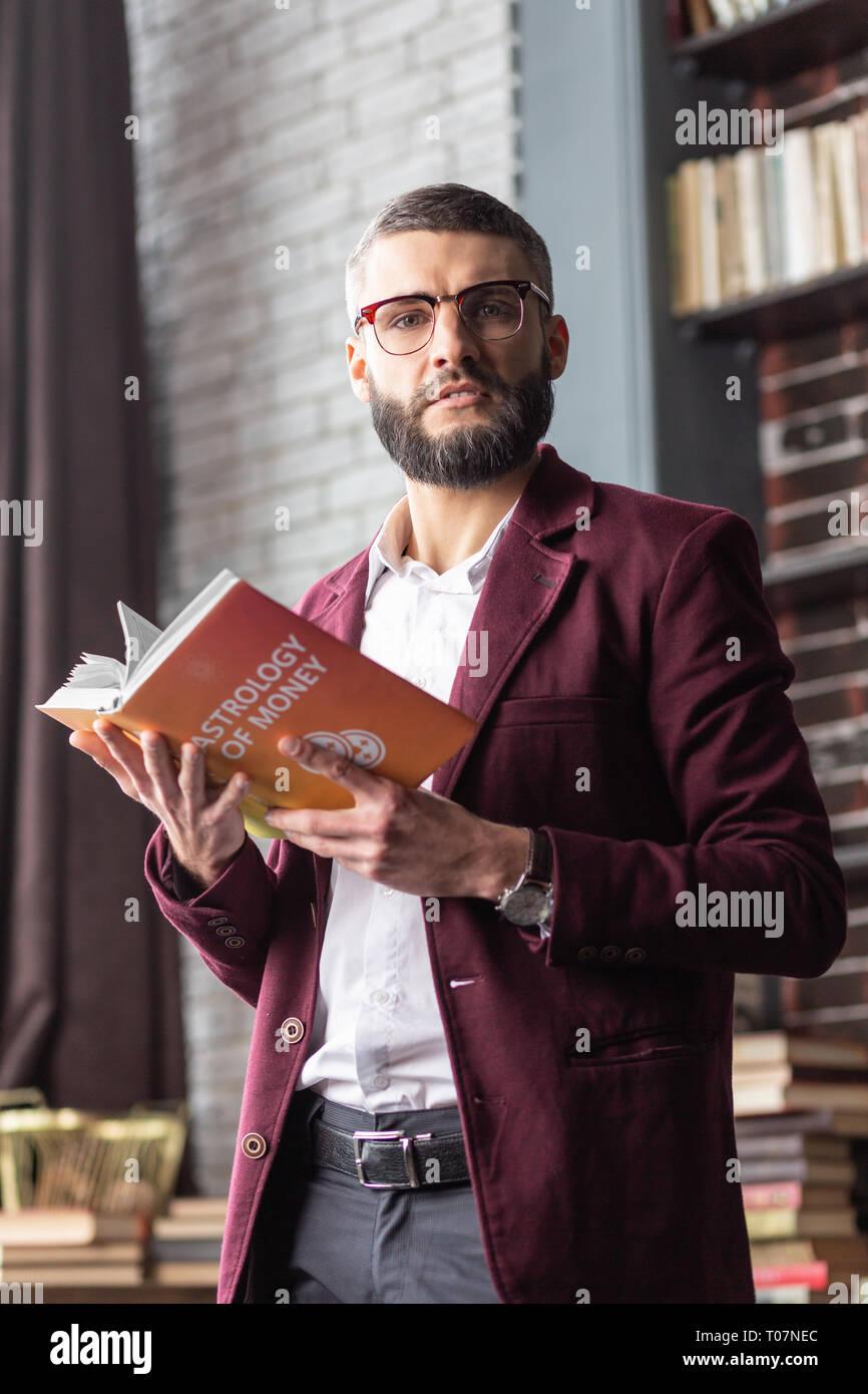 Successful businessman holding livre dans ses mains sentiment curieux Photo Stock