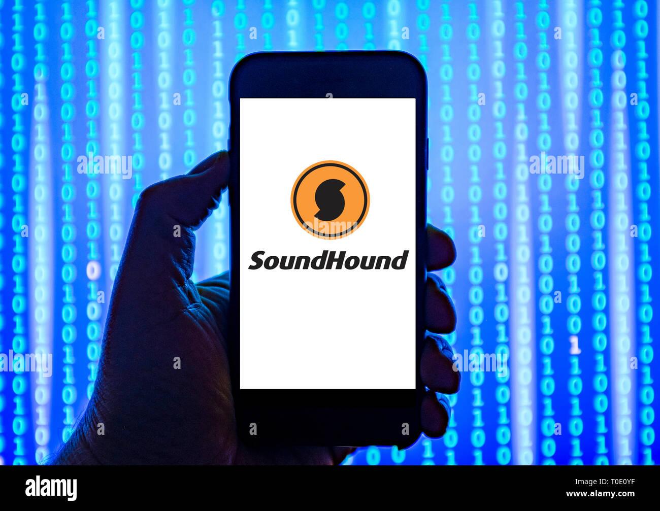Personne tenant smart phone avec Soundhound reconnaissance vocale et audio software company logo affiché sur l'écran. Photo Stock