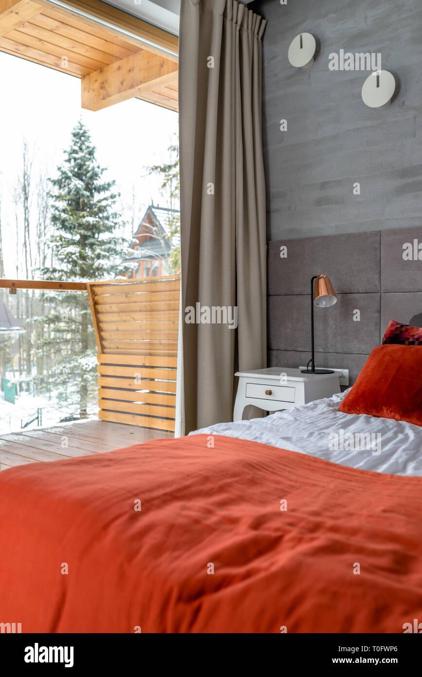 Chambre Avec Un Grand Lit, Oreillers Orange Disposés En Une Rangée, Mur  Recouvert De Gris Matériau Visible, Table Et Lampe De Chevet.