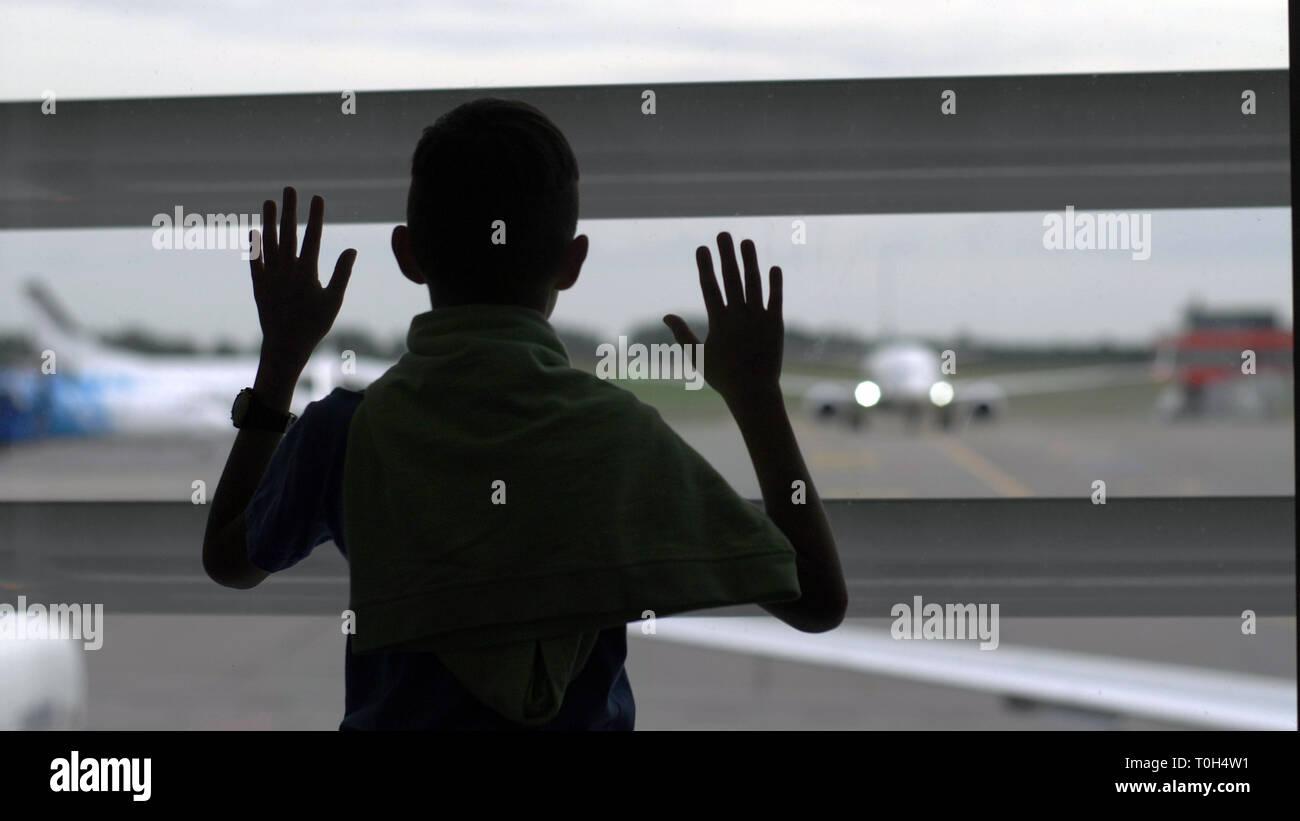 Boy stands près de la fenêtre à l'aéroport et il s'intéresse aux avions, le garçon rêve de devenir un pilote, s'amuser Banque D'Images