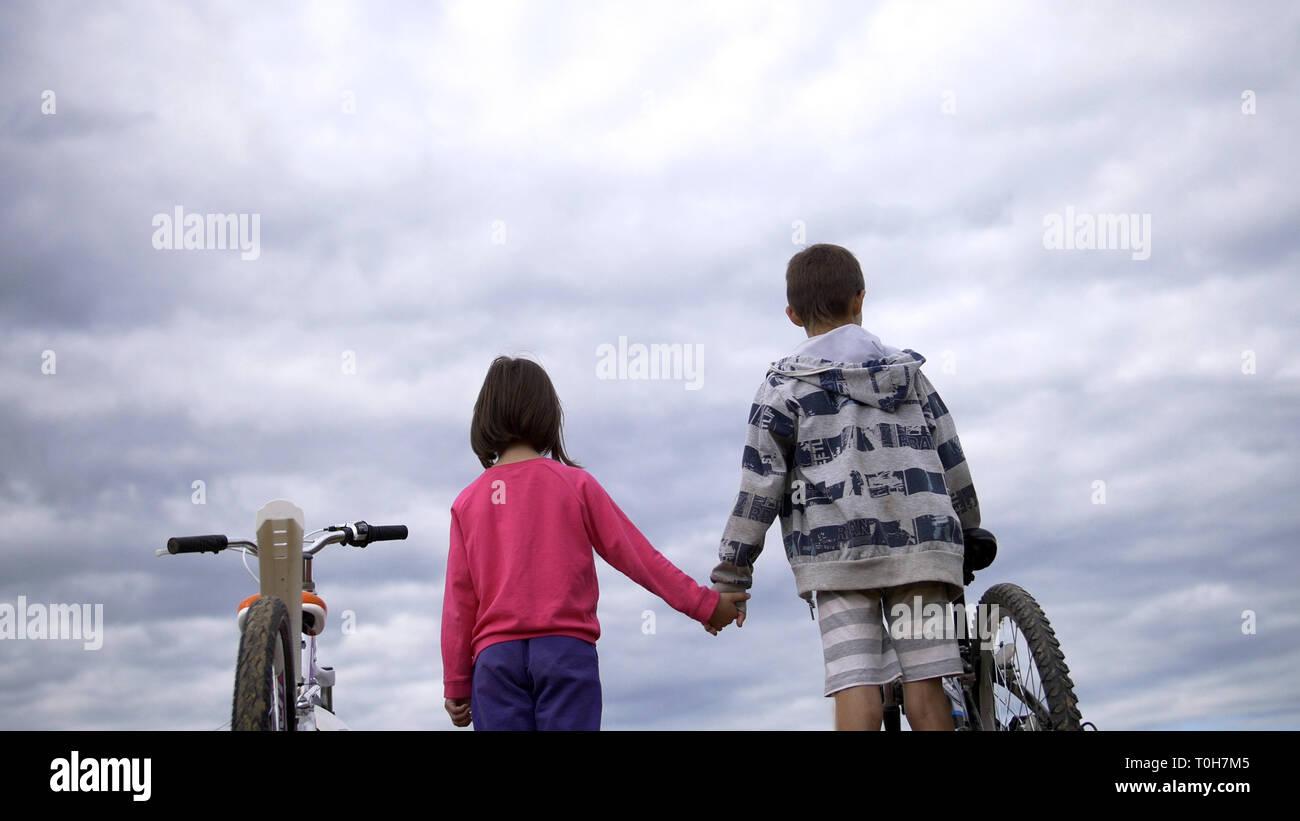 Garçon avec Girl standing avec des vélos sur le dessus et tenir la main sur le terrain Banque D'Images