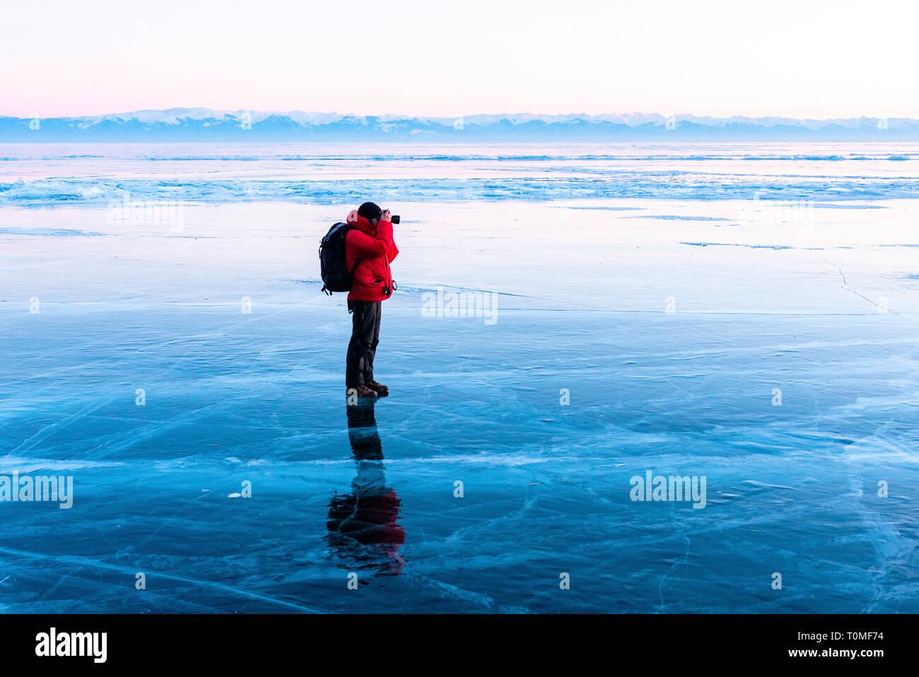 Photographe debout sur lac gelé, Lac Baikal, Sibérie, Russie Banque D'Images