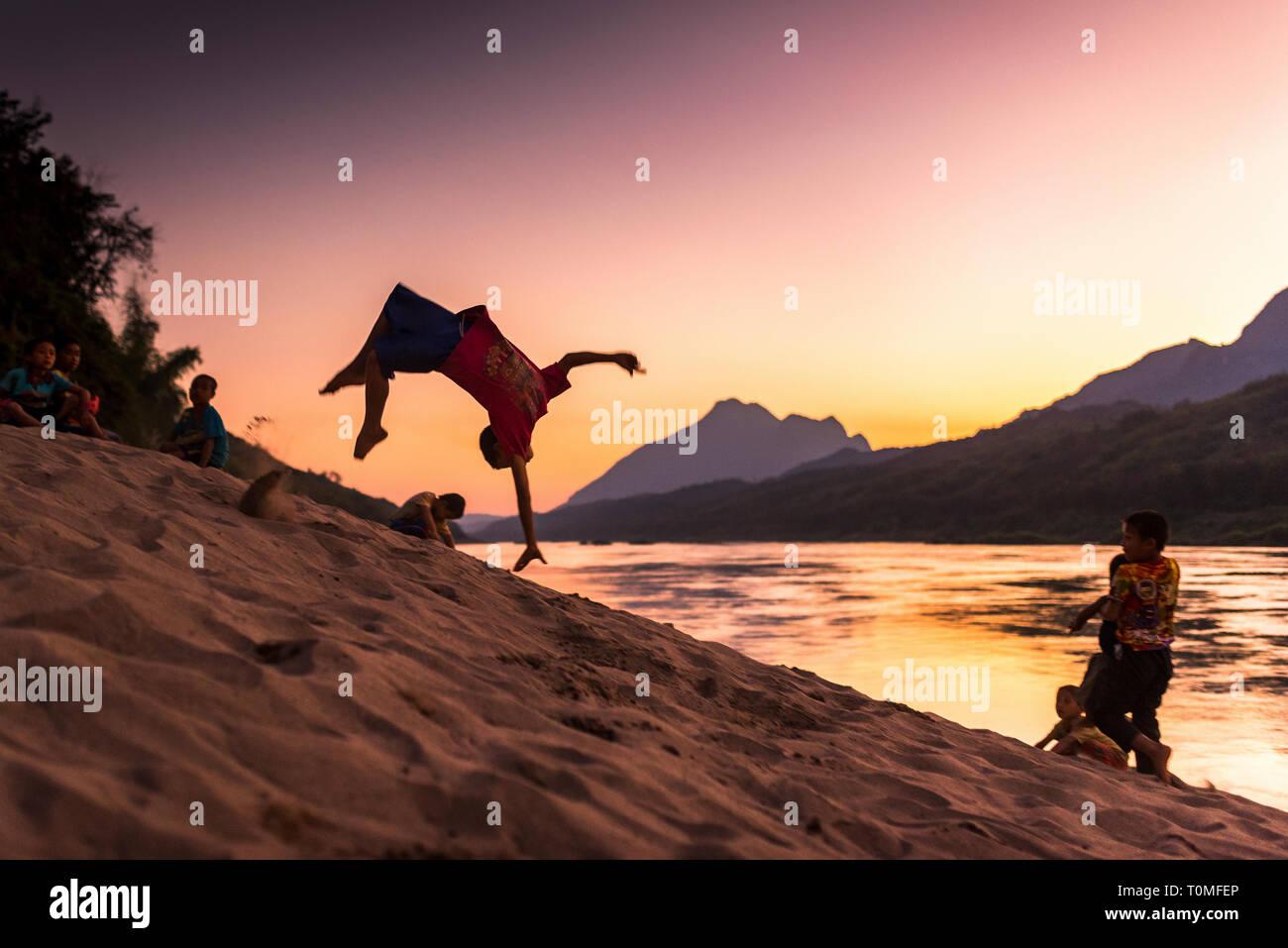 Backflip sur les rives du Mékong, au coucher du soleil, le Laos Banque D'Images