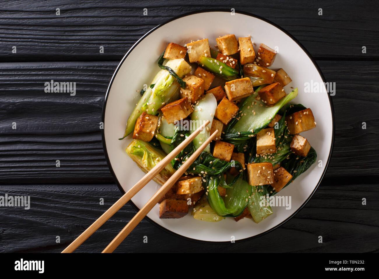 Tofu sauté avec bok choy et les graines de sésame sur une assiette sur la table. Haut horizontale Vue de dessus Banque D'Images