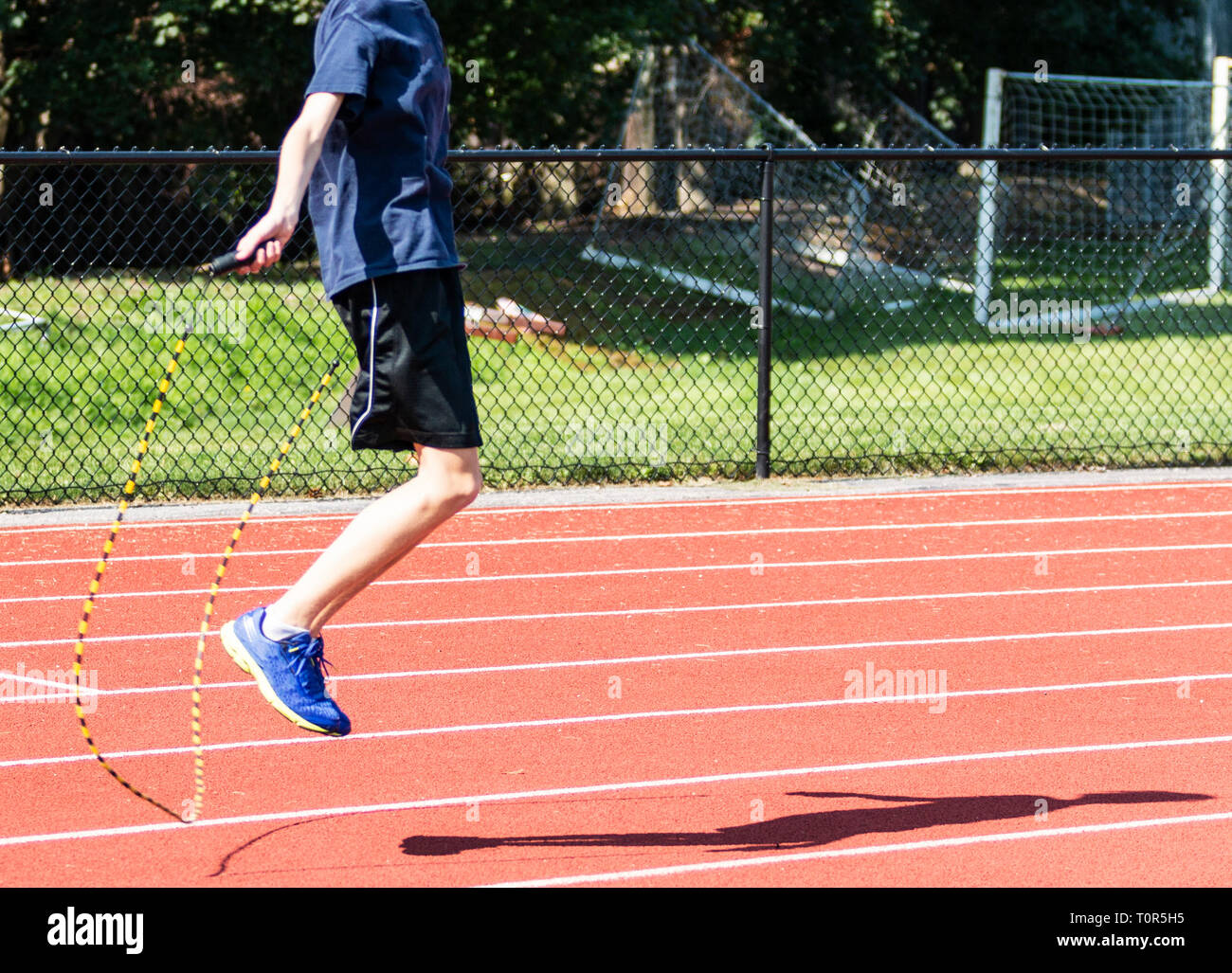 Une école runner est une formation polyvalente en sautant à la corde sur une piste à la fin de l'été. Photo Stock