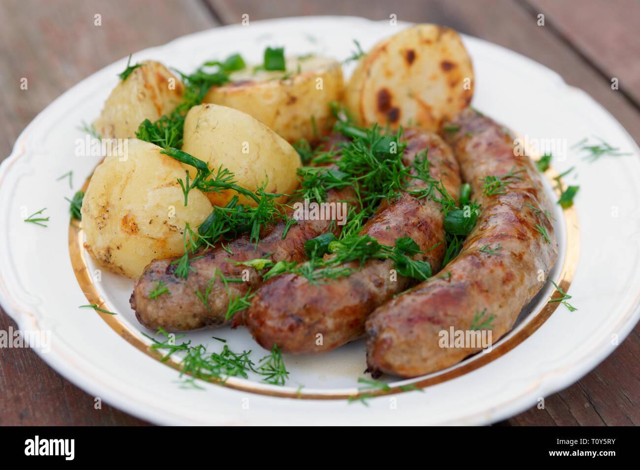 Saucisses grillées et de pommes de terre sur la plaque, close-up Banque D'Images