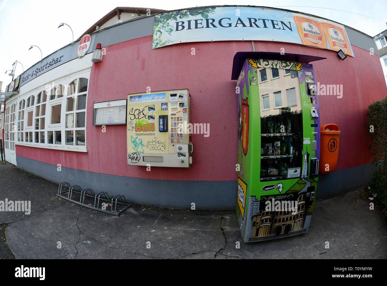 Trier, Allemagne. Mar 21, 2019. Un distributeur automatique de cannabis (r), qui contient des fleurs de cannabis séchées et pressées dans les sachets et extraire les perles dans des boîtes de plastique plus toutes sortes d'accessoires fumeurs à la vente, est situé sur la rue à côté d'un distributeur automatique de tabac. (Photo prise avec l'objectif fisheye) Ce sont des produits du chanvre avec la substance active CBD (cannabidiol), qui est considérée comme difficilement substances psychoactives. Credit: Harald Tittel/dpa/Alamy Live News Banque D'Images
