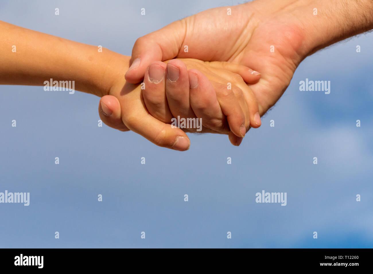 Reaching Out main dans la main. Un père à sa fille tenir la main avec un fond de ciel bleu. Photo Stock