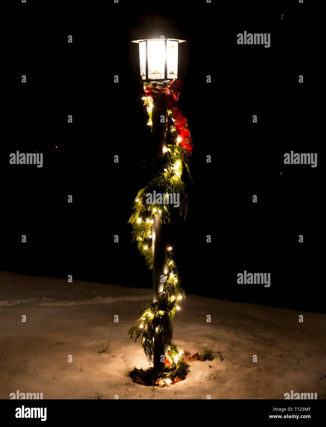 Un pôle d'éclairage est décoré de green garland s'enroulent autour du pôle avec les lumières de Noël attaché la nuit avec de la neige couvrant le sol. Photo Stock