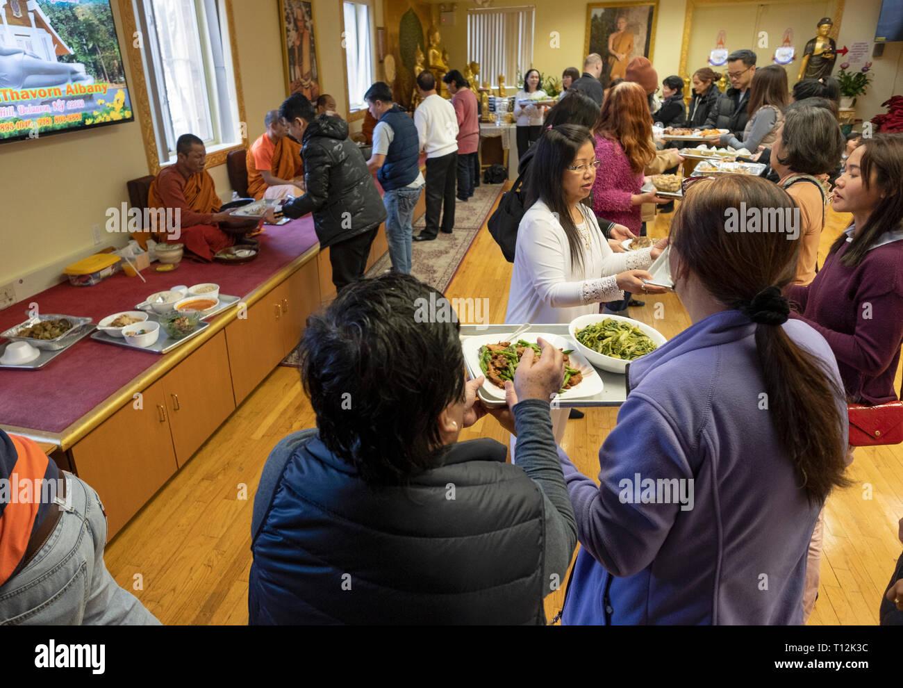 Fidèles à un temple bouddhiste forment une ligne d'assemblage pour servir la nourriture spécialement préparée à ses moines. Dans Elmhurst, Queens, New York. Photo Stock