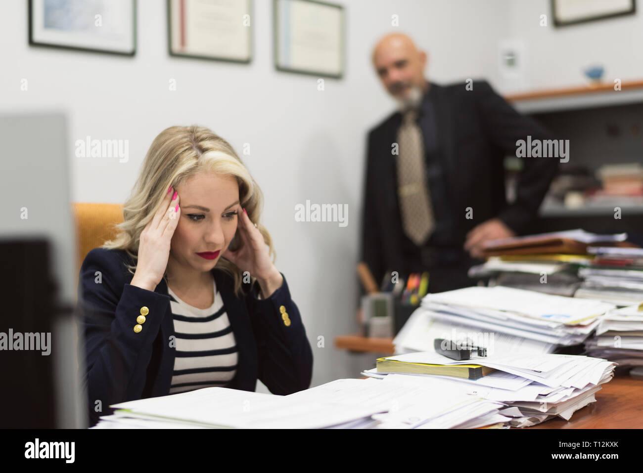 Female office worker a souligné devant une grande charge de travail de bureau et documents Banque D'Images