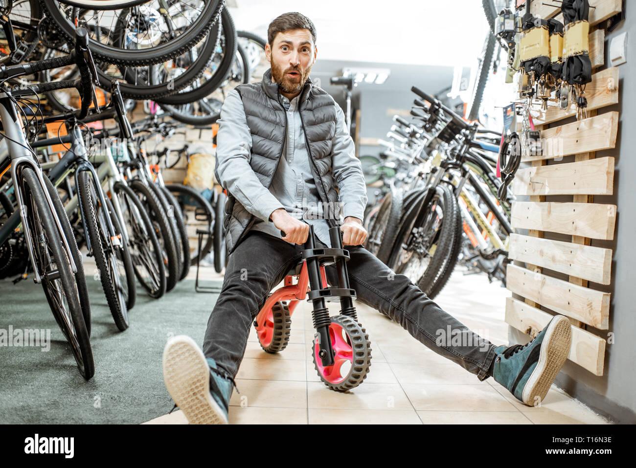 Portrait d'un homme drôle équitation children's location dans le magasin avec les vélos et les équipements sportifs Banque D'Images