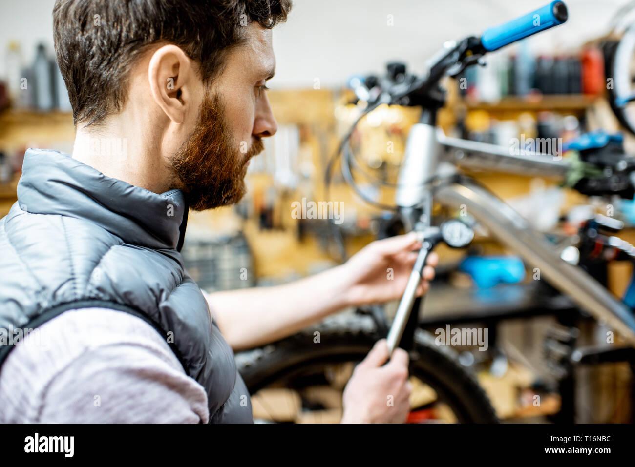 Réparateur au service d'une location, la vérification d'une pression de l'air dans l'amortisseur pneumatique d'une fourchette dans l'atelier Banque D'Images