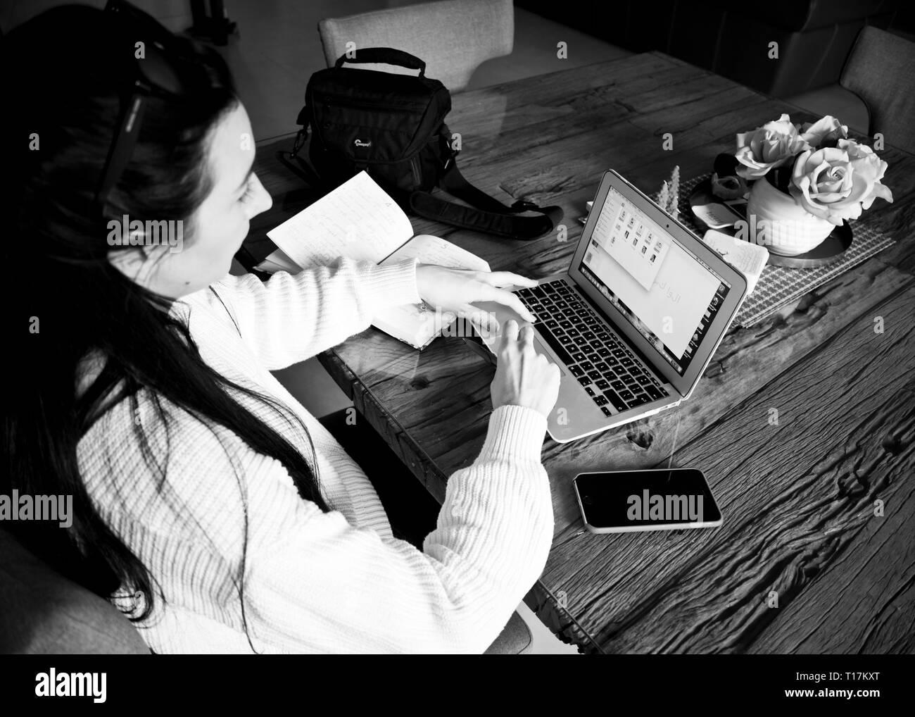 jeune femme entrepreneur travaillant assis à un bureau tapant sur son ordinateur portable dans un bureau à domicile, vue d'en haut prise en noir et blanc. Banque D'Images
