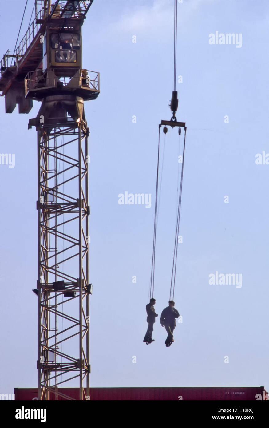 Archives des deux hommes dans le faisceau des travailleurs suspendus et abaissé par grue sur les contenants d'expédition en depot et brancher le câble de levage est de Londres Angleterre Royaume-uni Photo Stock