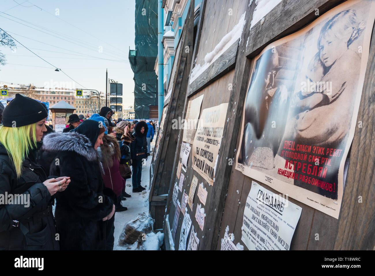 Les gens qui regardent les affiches soviétiques au cours de la 101ème anniversaire de la rupture de Blocus de Leningrad 1918, dans les rues de Saint-Pétersbourg (Russie). 90 Photo Stock