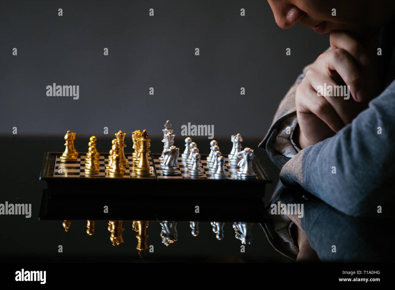 Cropped shot of man se frottant le menton et la réflexion sur prochain déplacement tout en jouant aux échecs sur une table en verre sur fond gris Banque D'Images
