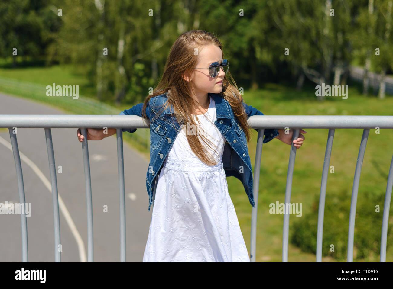 a72fc3648e60f Portrait de belle petite fille en robe blanche en veste en jean bleu et des  lunettes