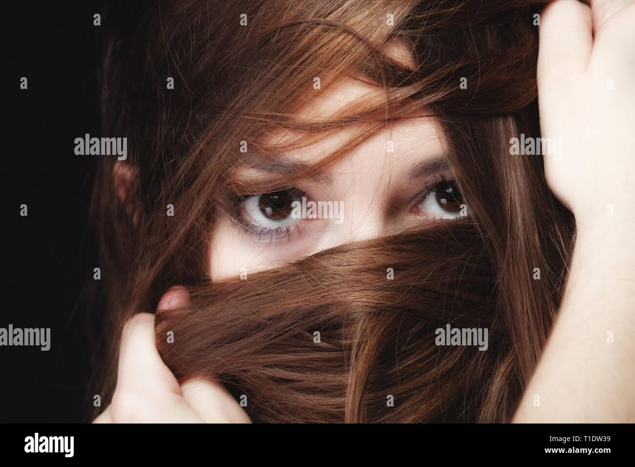 La solitude et l'anxiété stress femmes concept. Closeup portrait belle femme aux cheveux sombres, teen girl covering face par de longs poils bruns sur noir Banque D'Images