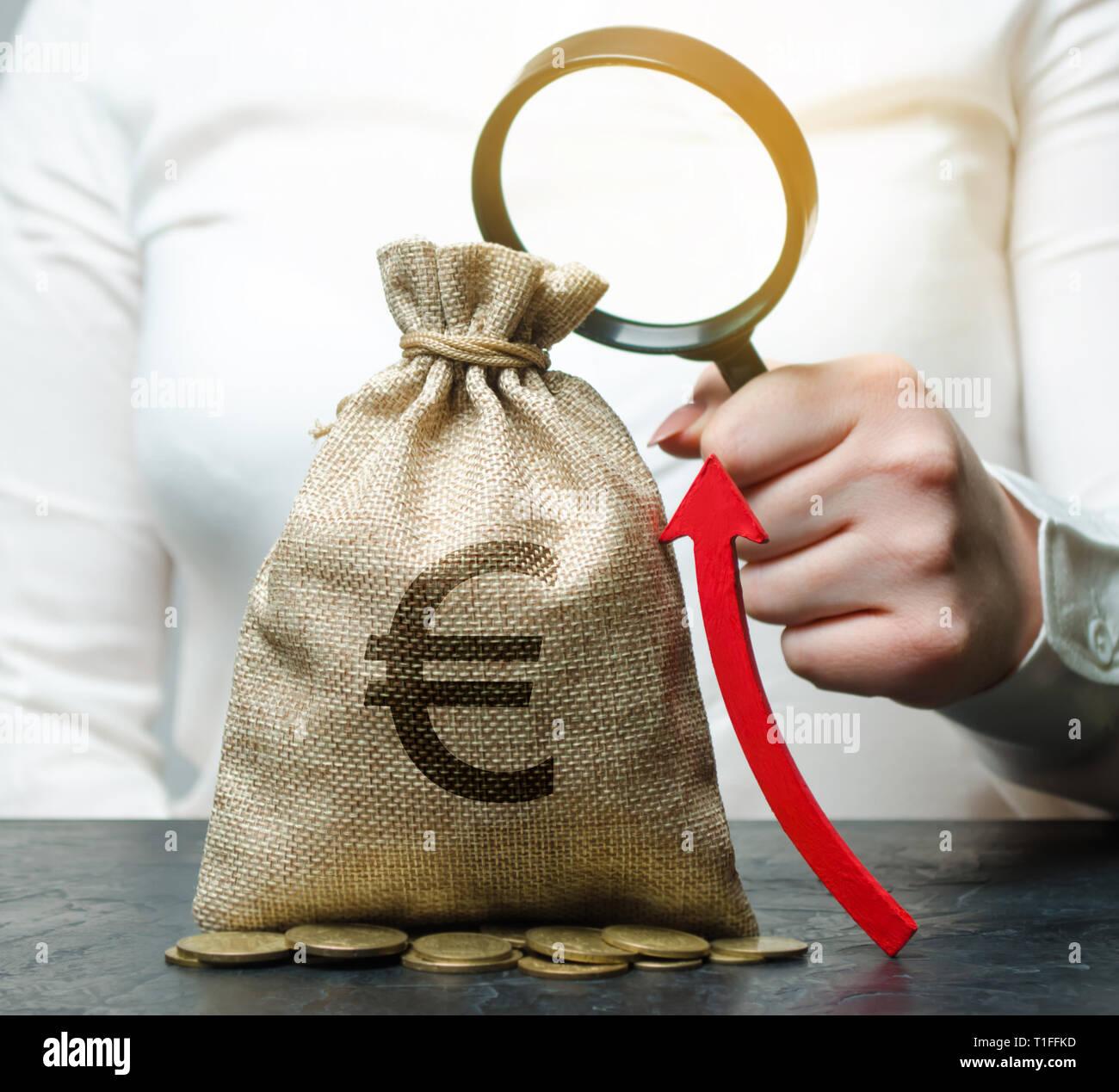Femme main courante loupe sur sac d'argent et la flèche vers le haut. L'analyse de concepts de profits et de budget dans la société. Réussite de l'entreprise. L'ensemble, les Banque D'Images