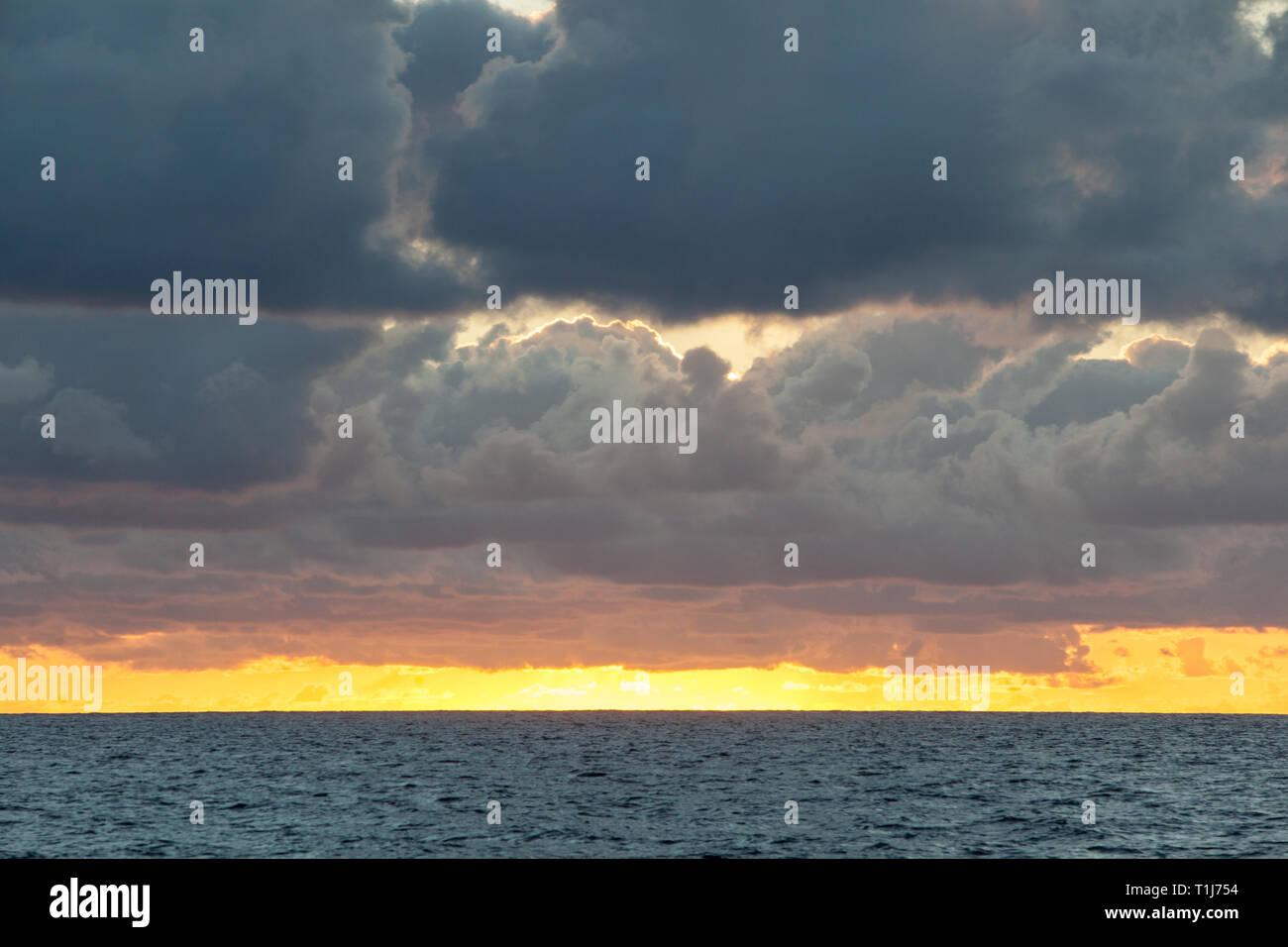 Un magnifique lever du soleil illumine les nuages au-dessus de la dérive sur la mer des Caraïbes. Banque D'Images