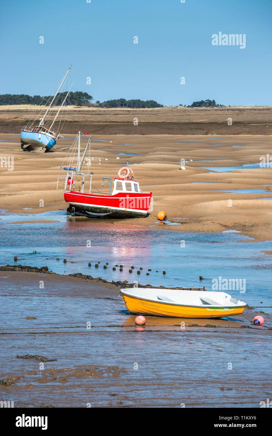 Bateaux colorés sur les bancs de sable à marée basse sur les marins de la flotte et de l'estuaire de la rivière au Wells next the sea, North Norfolk Coast, East Anglia, Angleterre, Royaume-Uni. Banque D'Images