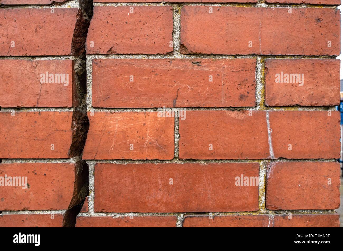 Très gros 12.7mm ou 1/2 pouce fissure allant verticalement vers le bas la division d'un mur de brique rouge en deux Photo Stock